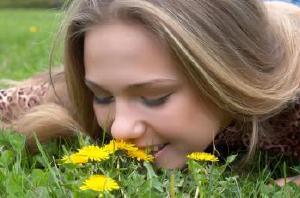 pretty girl smells dandelion